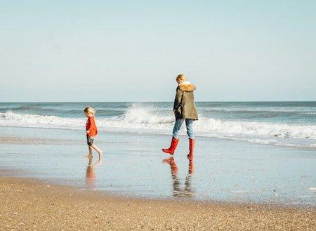 Coast walk - A Lady and child paddling by the sea shore