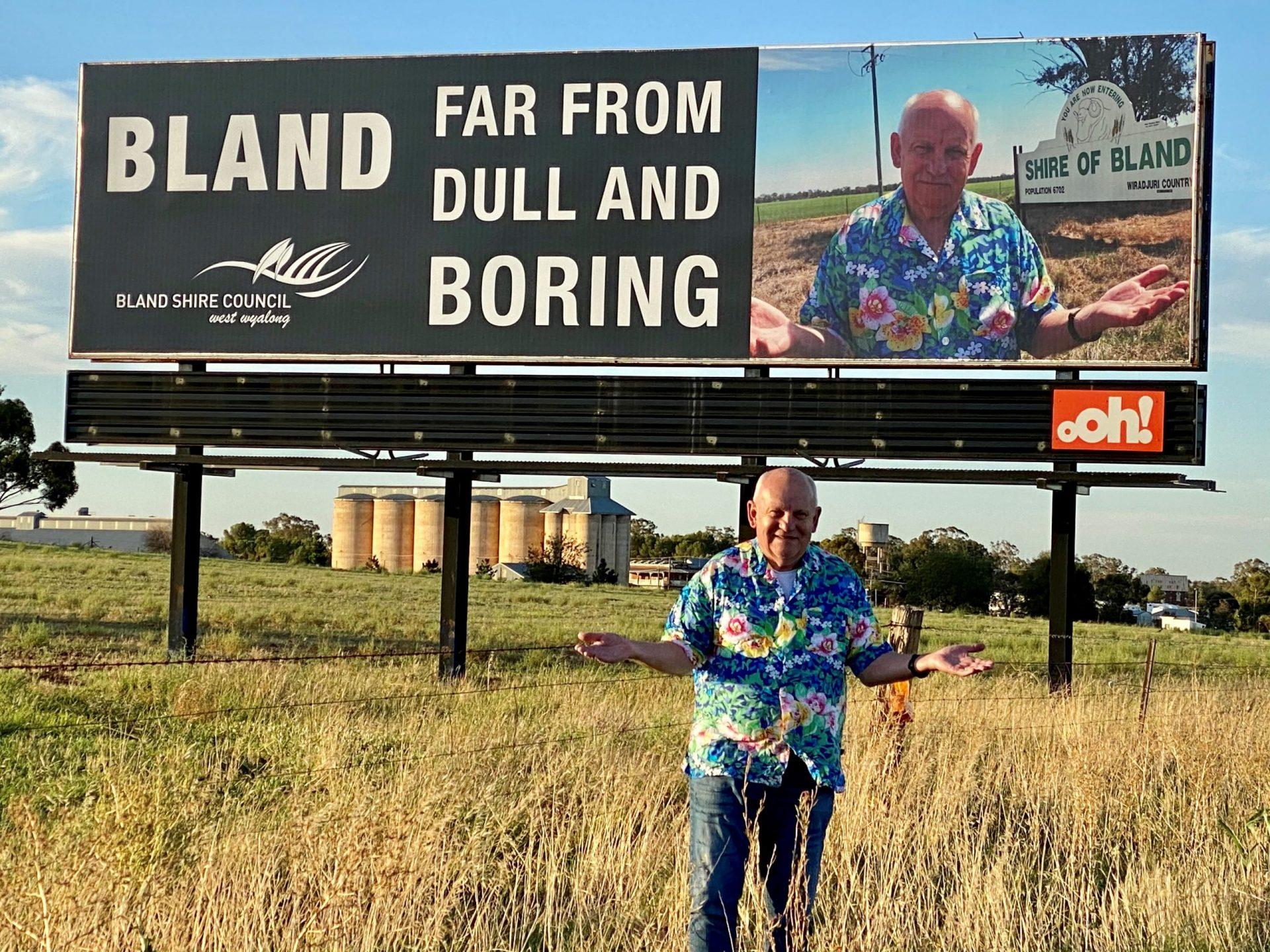 Bland Shire Council's General Manager, Ray Smith, at the the Bland, Dull and Boring billboard on the Newell Highway, Bland Shire, Australia. Image taken by Donna Smith