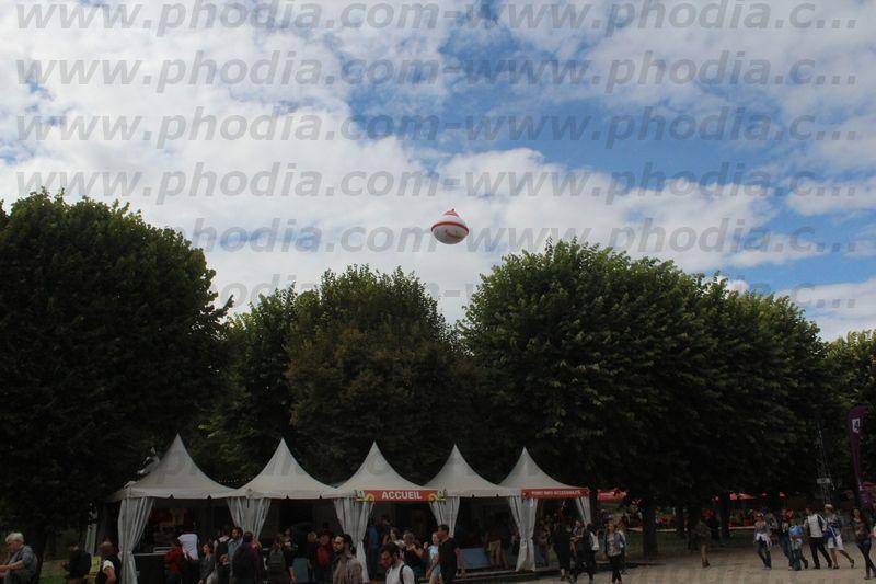 soucoupe kronenbourg helium en l'air au dessus des arbres