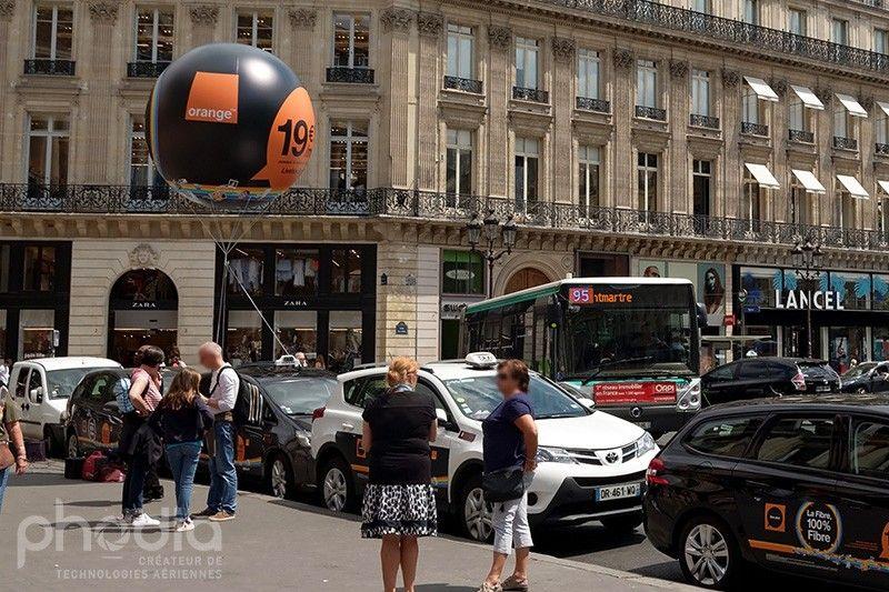ballon pub hélium de 2.5m de diamètre pour l'opérateur orange fixé sur une voiture le long d'un trottoir
