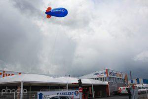 dirigeable bleu, ailerons rouge avec marquage Eleclerc, au dessus d'un super marché