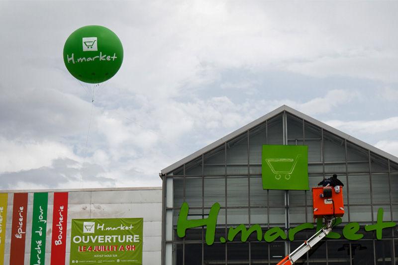 ballon helium vert 250cm devant un magasin hmarket