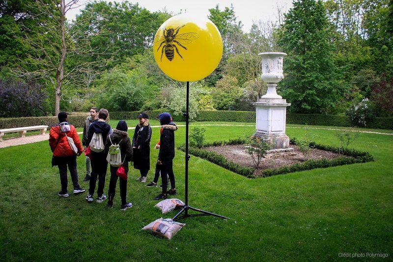 Des collégiens au château de Versailles devant un ballon sur trépieds jaune de 80cm