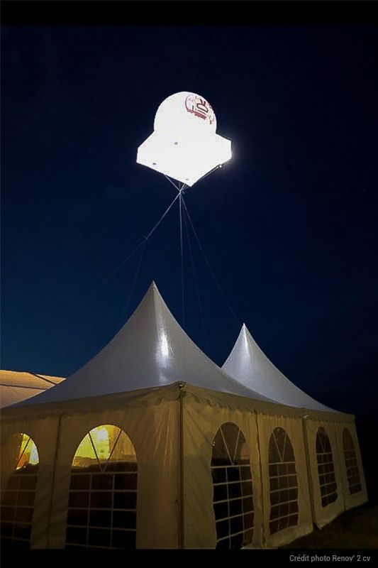 ballon pub géant lumineux au dessus d'un stand