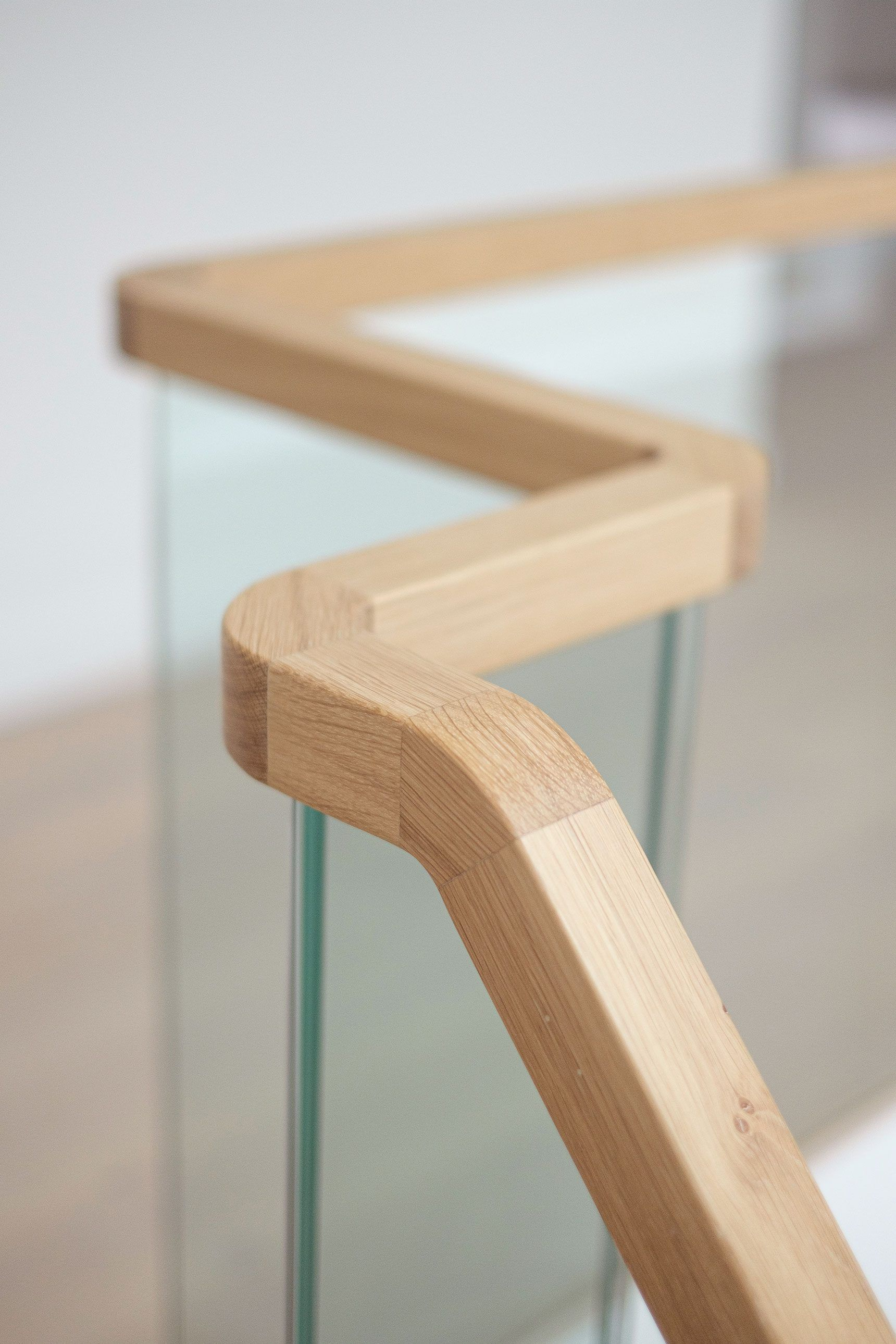 Square section oak handrail on a glass balustrade.