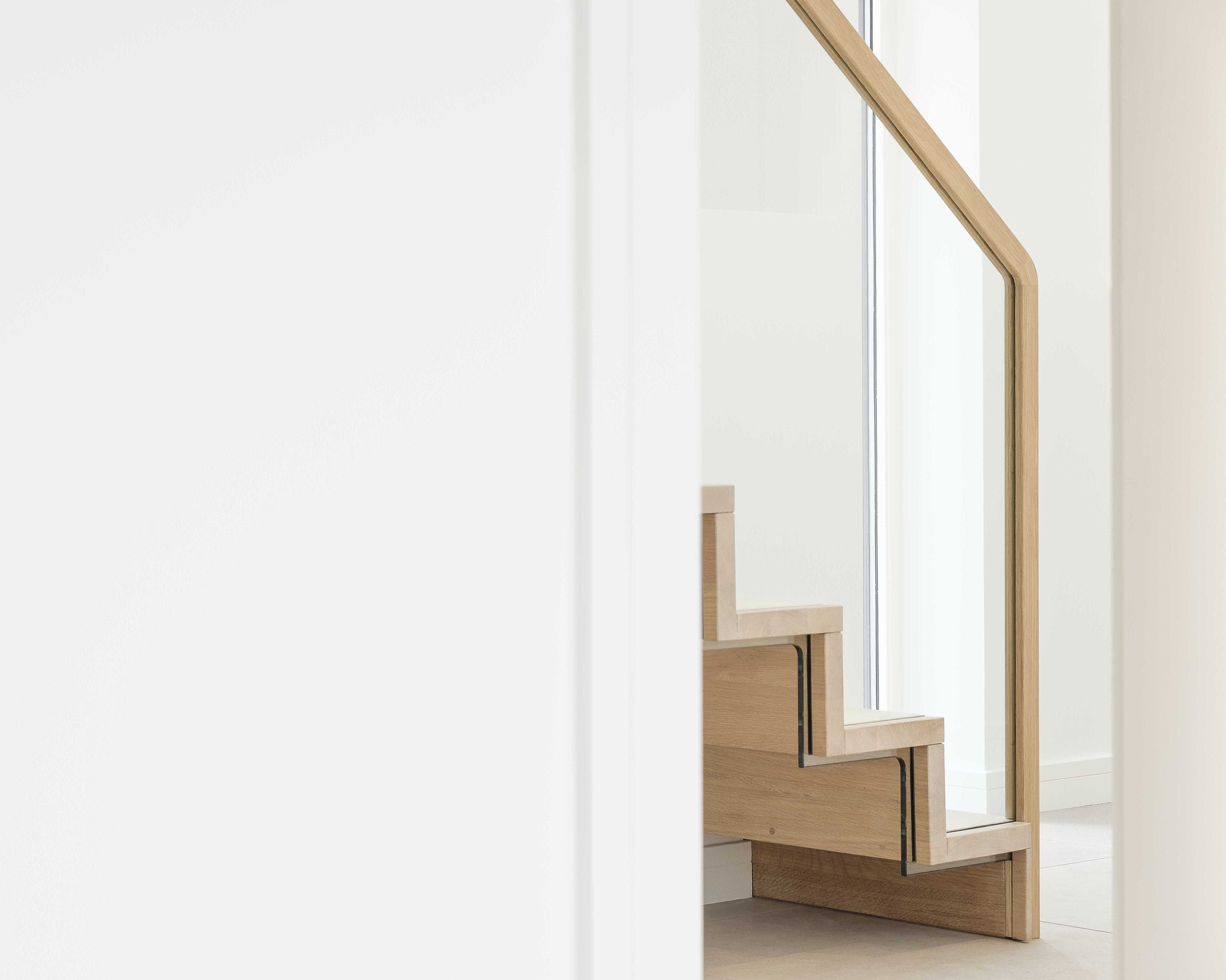 Side view of slim profile cantilevered oak staircase handrail and glass balustrade.