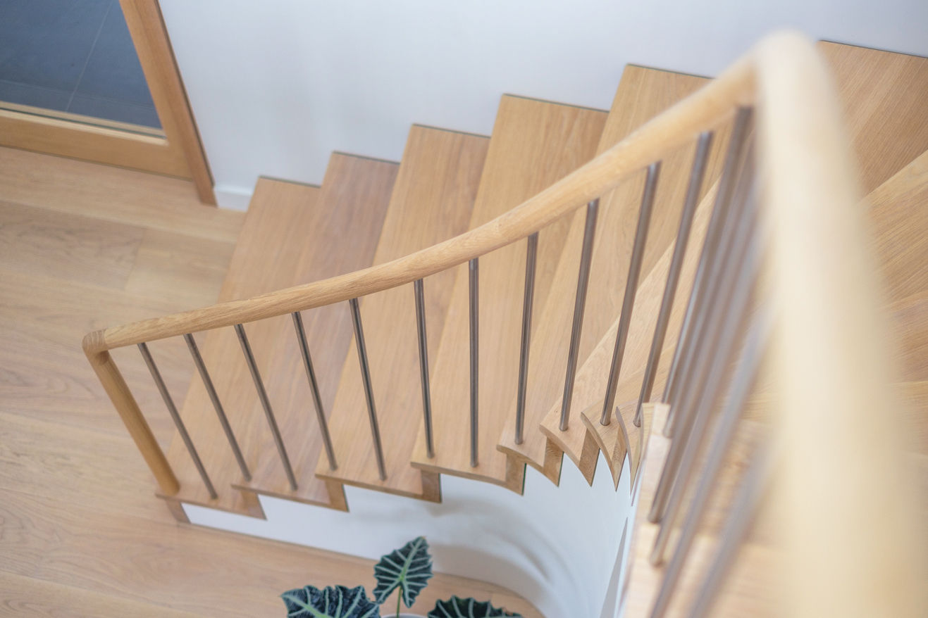 Soft focus oak staircase and oak handrail, with stainless steel spindles. Plant slightly out of shot.
