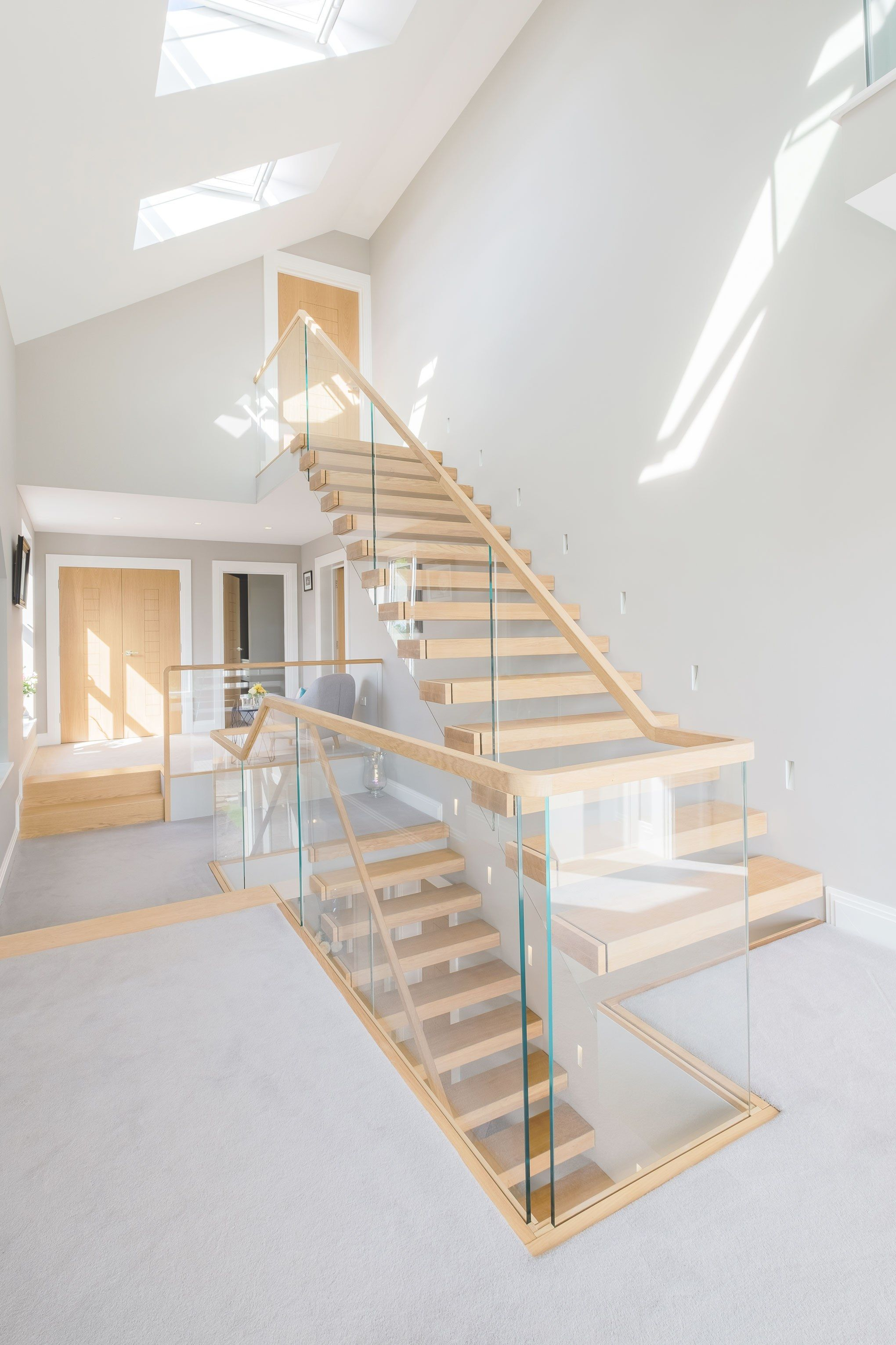 View of triple height floating cantilevered oak stair with glass balustrade. Grey walls and carpet with wood doors. Two large skylights.