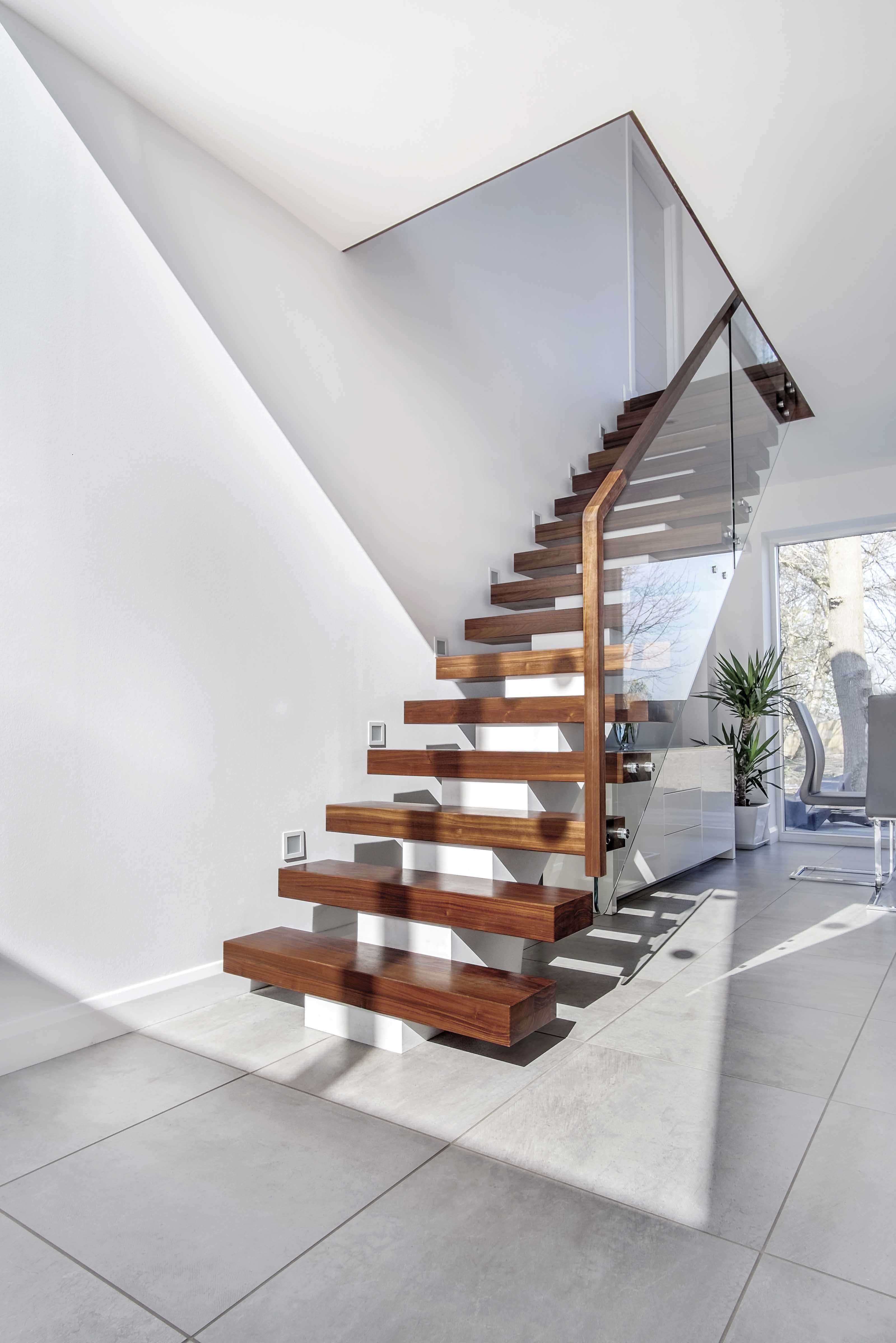 Modern domestic interior with floating central stringer feature staircase with walnut treads, handrail and glass balustrade. White walls with grey floor tiles and large potted plant.