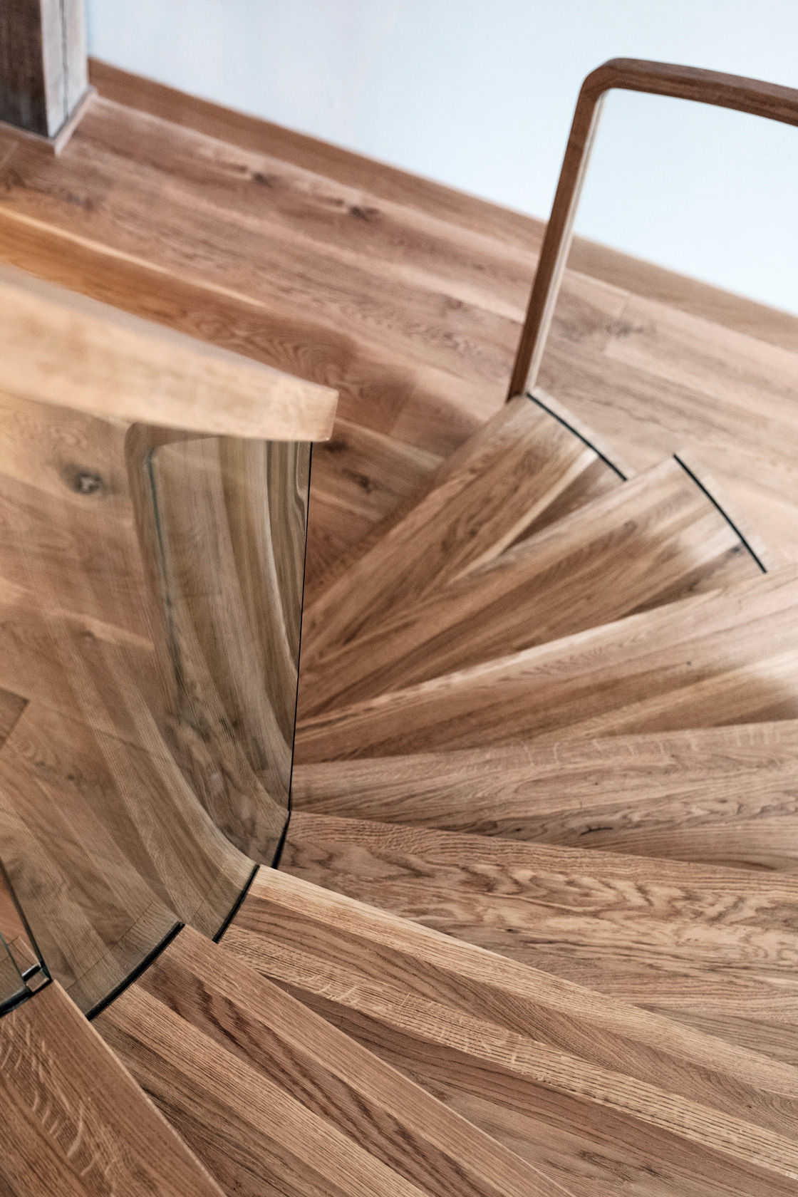 Looking downwards view of curved oak staircase centrepiece with curved glass and curved handrails.