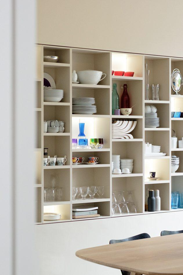 Bespoke display and storage shelving filled with glassware and ceramics. Wooden table and black light fixture.