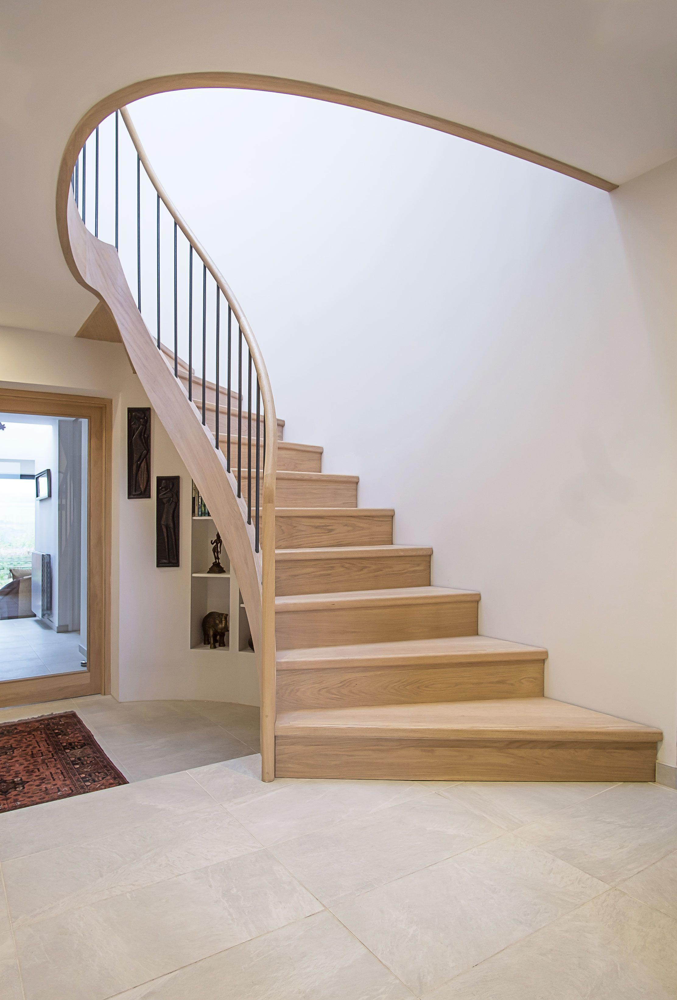 Ground floor view of feature Elliptical oak stair with iron balustrade and oak handrail. Tiled floors, rug, glazed oak doors and storage..