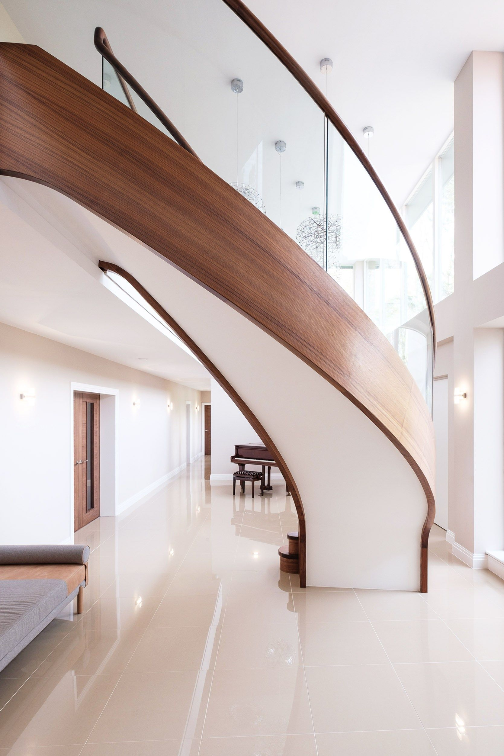 Underside of view of sweeping curved walnut stair with curved glass in large home with baby grand piano.