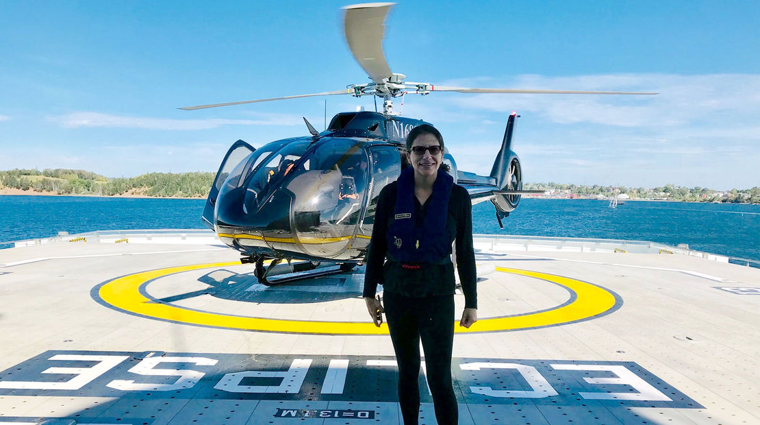 Travel Weekly's Johanna Jainchill in front of the Scenic Eclipse's helicopter just after landing on the ship's stern.