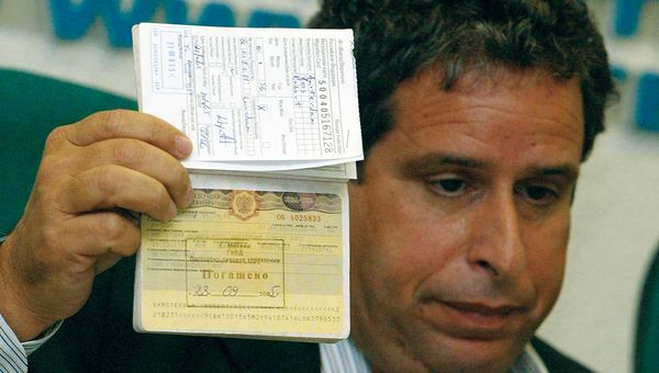 Robert Amsterdam, Canadian attorney for Russian oil tycoon Mikhail Khodorkovsky, shows his passport with his Russian visa annulled at a news conference in Moscow in September 2005. A group of Russian Federal Security Service officers had arrived at Amsterdam's hotel room in the middle of the night and taken away his passport, he said. When they returned the passport, his Russian visa had been annulled, and he was ordered to leave the country.