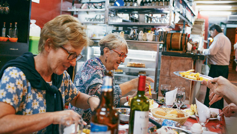 Leora Benjamin, left, and Isobel Lamont feast at a traditional restaurant in the San Telmo neighborhood of Buenos Aires with Peregrine Adventures.