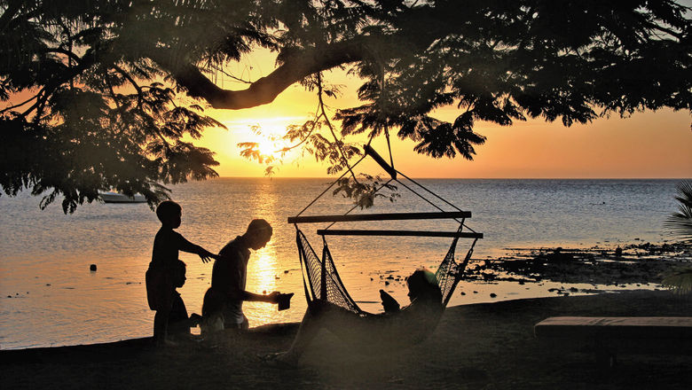 A family at dusk on the waterfront of the Volivoli Beach Resort.