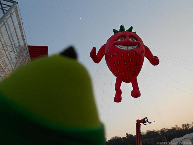 grosse fraise énorme de 8m avec une bouche et des bras pour faire de la publicité