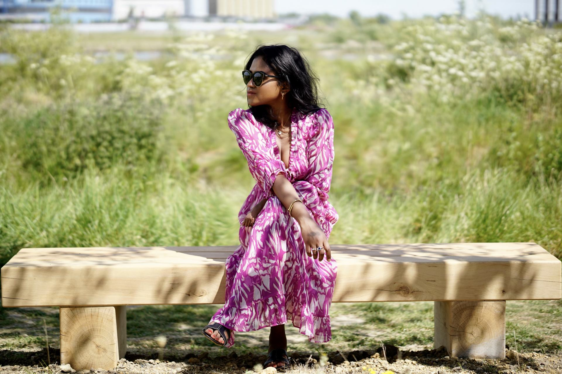 Sachini sitting on a bench in the nature wearing a white and pink dress