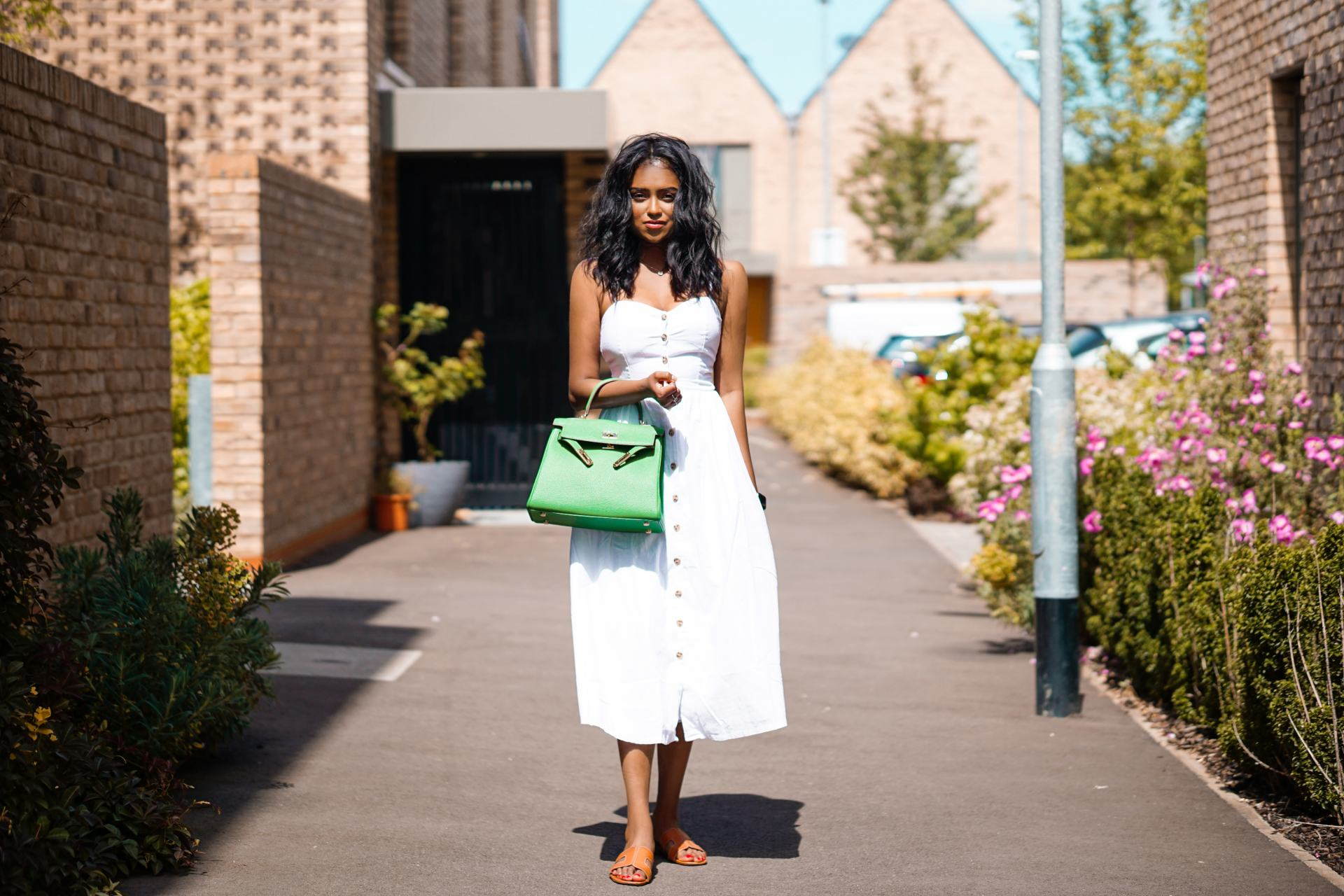 Sachini on a side walk wearing a white dress and a green Lily and Beans bag
