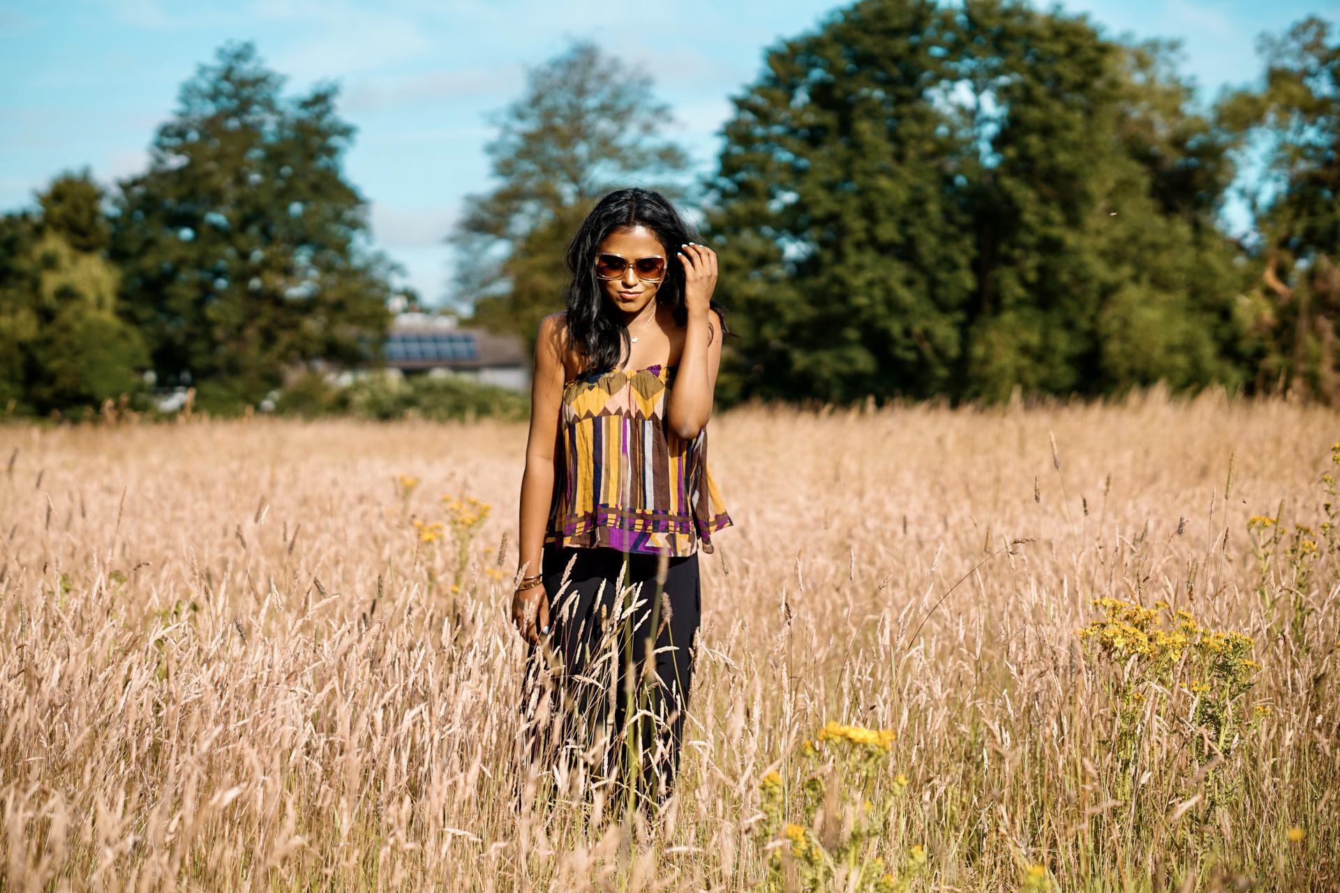 Sachini standing in a golden wheat field wearing a colourful ba-sh top and black trousers