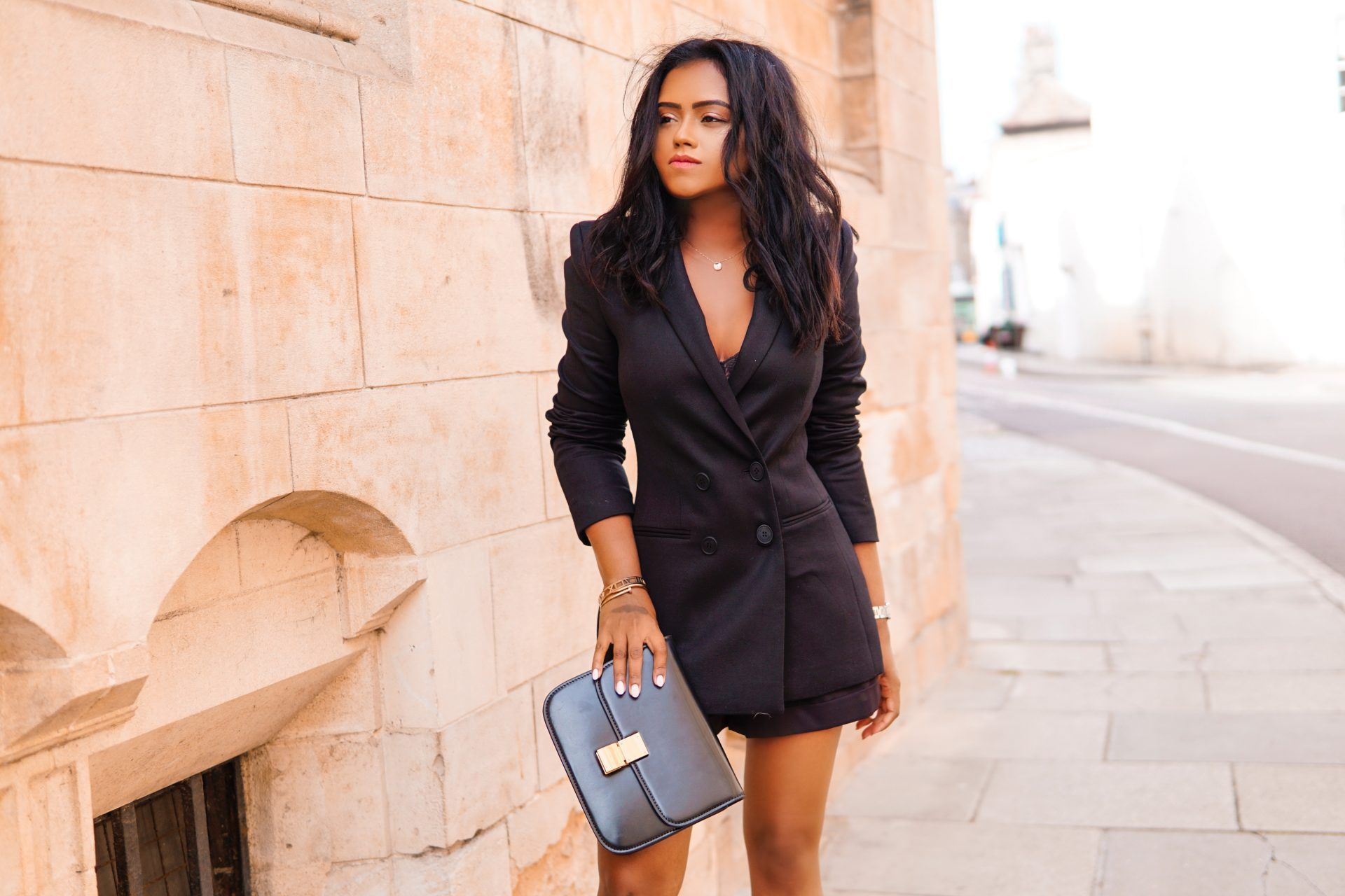 Sachini wearing a black Saint and Sofia blazer with black shorts and black handbag, standing in front of a building