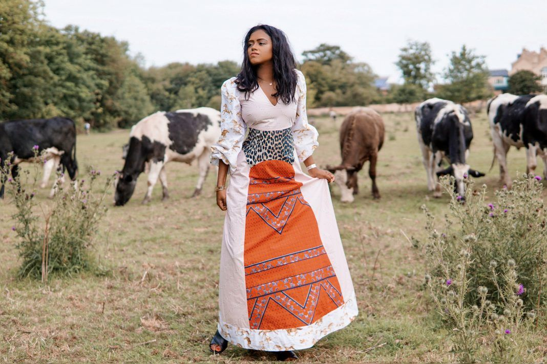 Sachini standing in the fields wearing a red and white Ganni dress with cows in the background