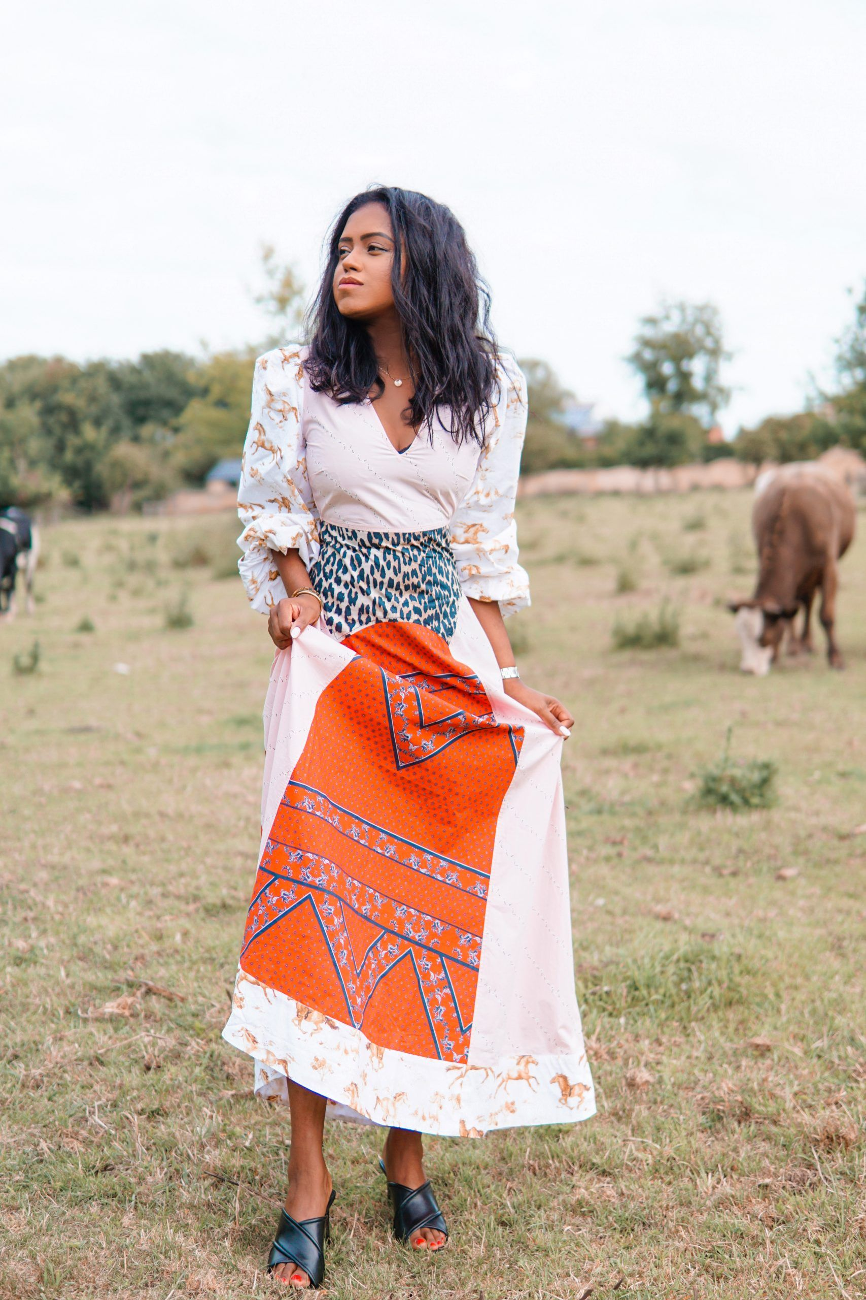 Sachini standing in the fields wearing a red and white Ganni dress