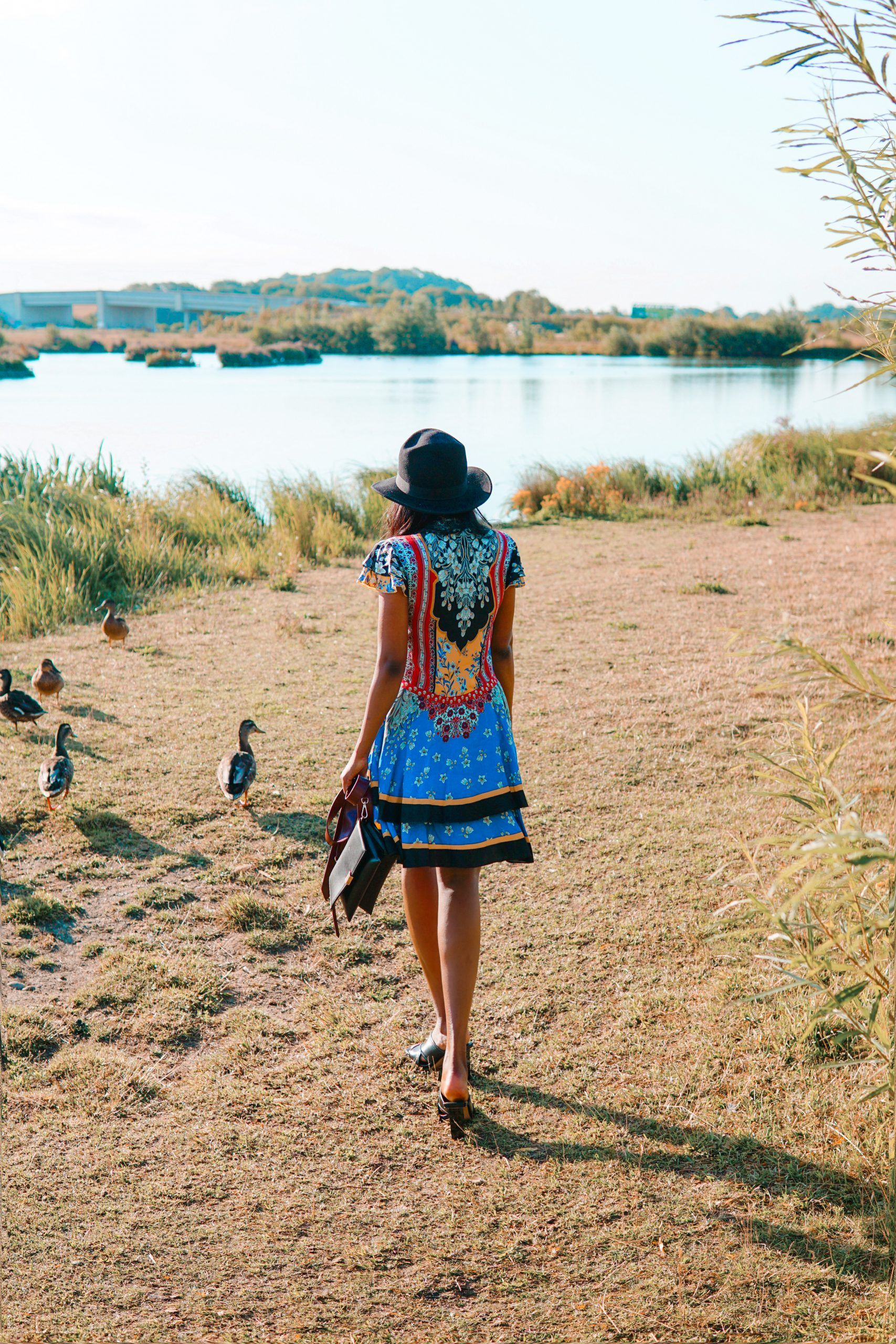 Sachini walking towards a lake with blue and red Alice and Olivia dress