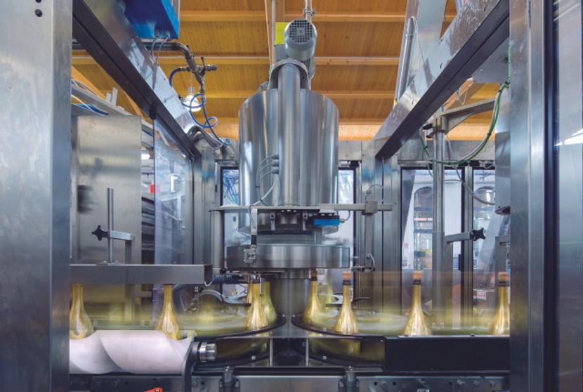 Eine spezielle Maschine verschliesst die mit Prosecco gefüllten Flaschen mit einem Kronenkorken.