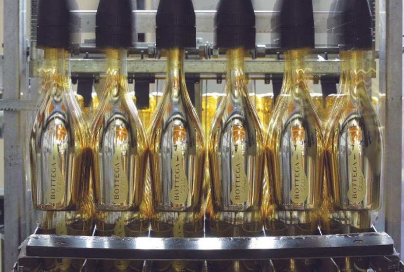 Die Flaschen werden mit einer Aluminium Kapsel versiegelt und kommen auf das Laufband.