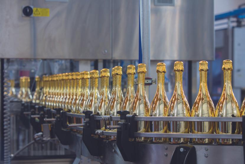 Die Flaschen werden auf dem Laufband in 6er Gruppen angeordnet.