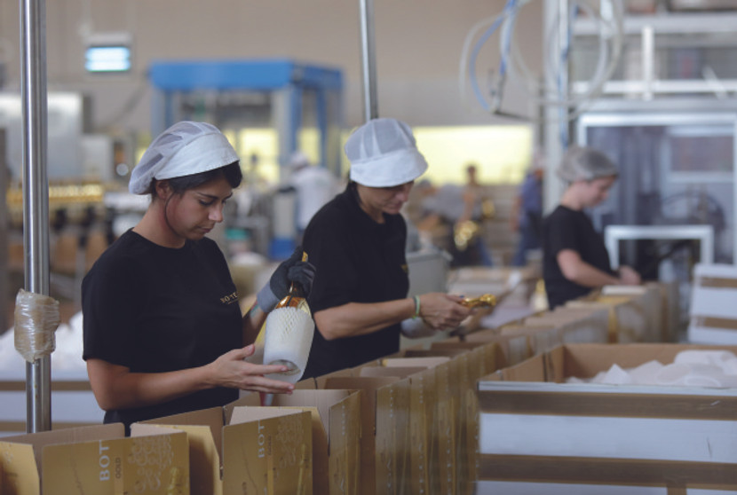 Manuell wird jede einzelne Flasche mit einer weichen Schutzhülle versehen, damit beim Transport keine Kratzer entstehen.