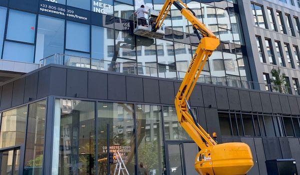 Adhesif decoupe blanc pose sur facade immeuble travaux nacelle