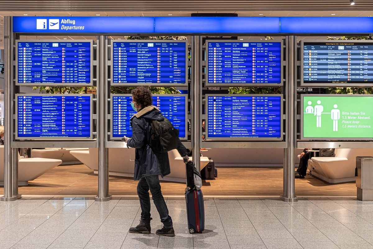 Man with mask at airport getting ready for summer travel