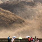 Turisták bámulják a kínai Hsziaolangdi gát megnyitását (2012.) Fotó: Str / AFP