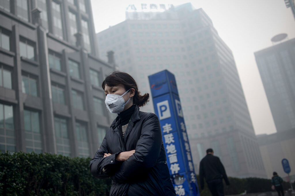 A woman wearing a mask walks past in Beijing on November 30, 2015. Beijing choked under the worst smog of the year on November 30, with dangerous particulates nearly 20 times healthy levels, as China's president joined other leaders in Paris for key climate change talks. AFP PHOTO / WANG ZHAO / AFP / WANG ZHAO