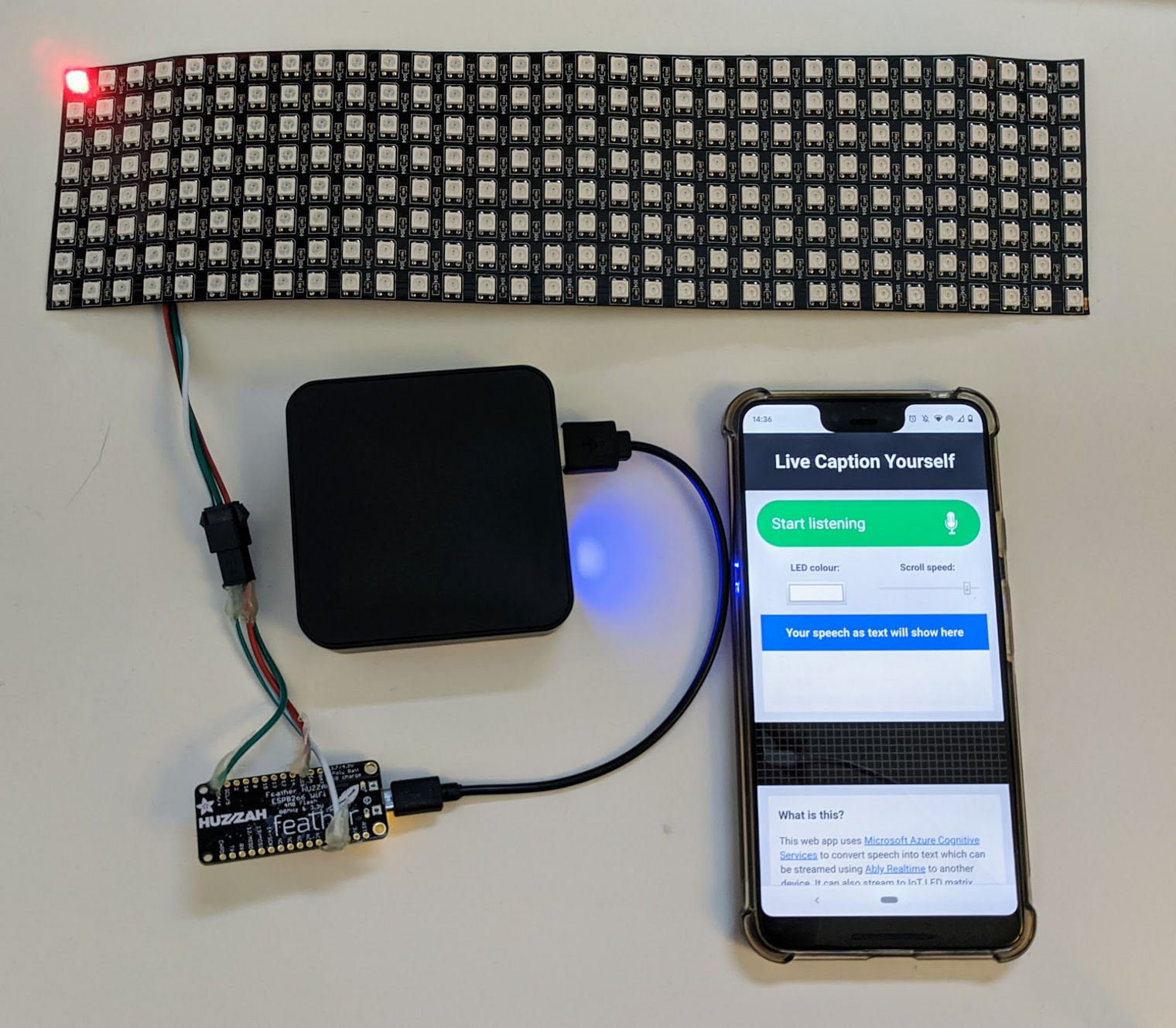 A flexible display attached to an Adafruit Feather Huzzah connected to a USB battery and a phone displaying the app