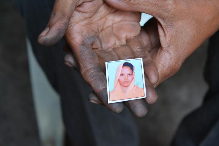 Raisa Begum holds a photograph of her daughter Razia. Photo by Sufian Farooqui.