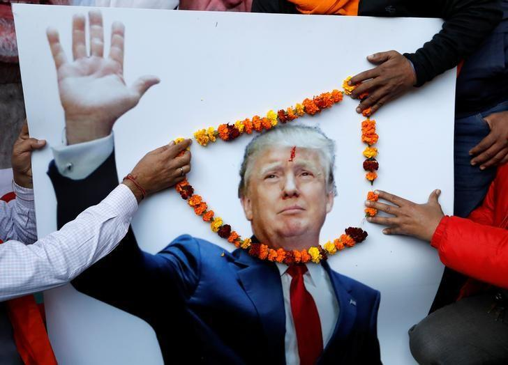 Members of Hindu Sena, a right-wing Hindu group, place a garland on an poster of U.S President-elect Donald Trump ahead of his inauguration, in New Delhi, January 19, 2017. REUTERS/Cathal McNaughton/Files