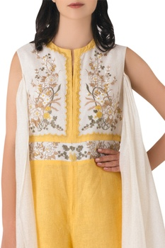 Yellow linen embroidered jumpsuit with attached drape.