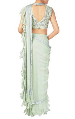 Green georgette ruffle layer sari with sleeveless blouse