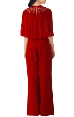 Red georgette jumpsuit with embroidered floral motifs.