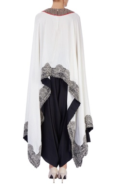 White embroidered cape with black pants
