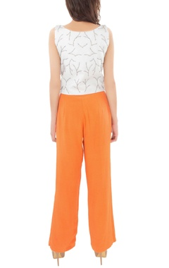 white beadwork crop top with orange trousers