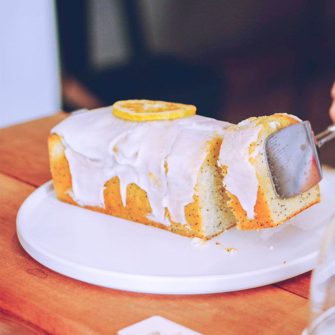 CBD infused lemon drizzle cake in the white plate