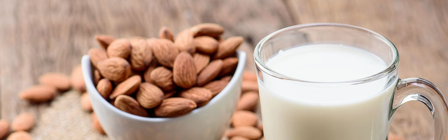 A cup of CBD infused almond milk and a small bowl of almonds