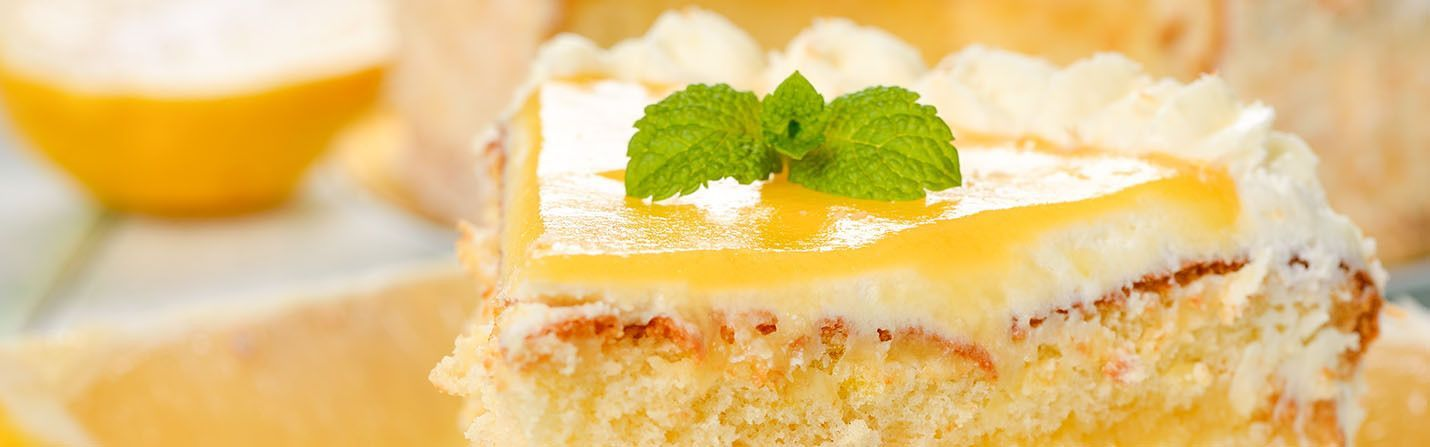 A piece of CBD lemon cake with white cream and mint on top