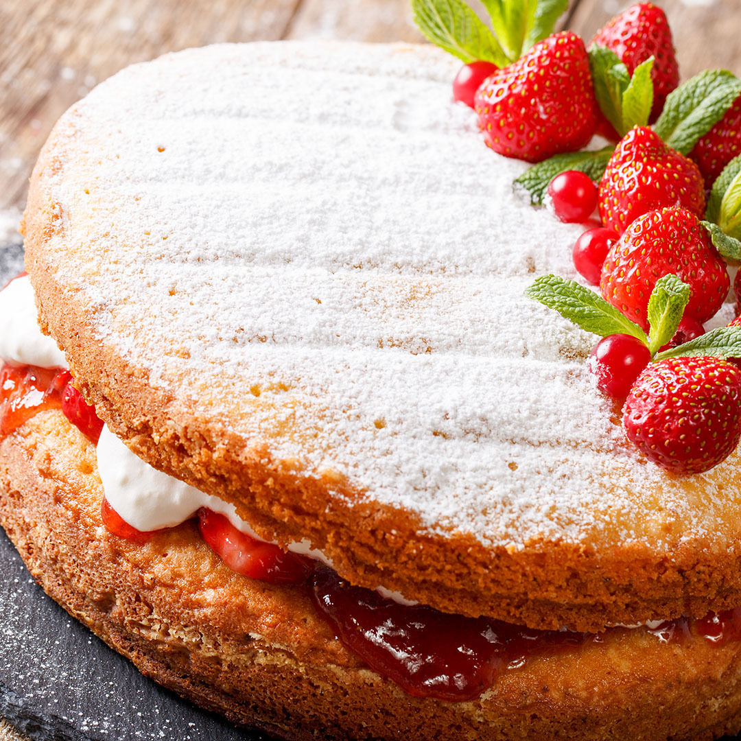 CBD infused classic Victoria Sandwich with strawberries and sugar powder on it