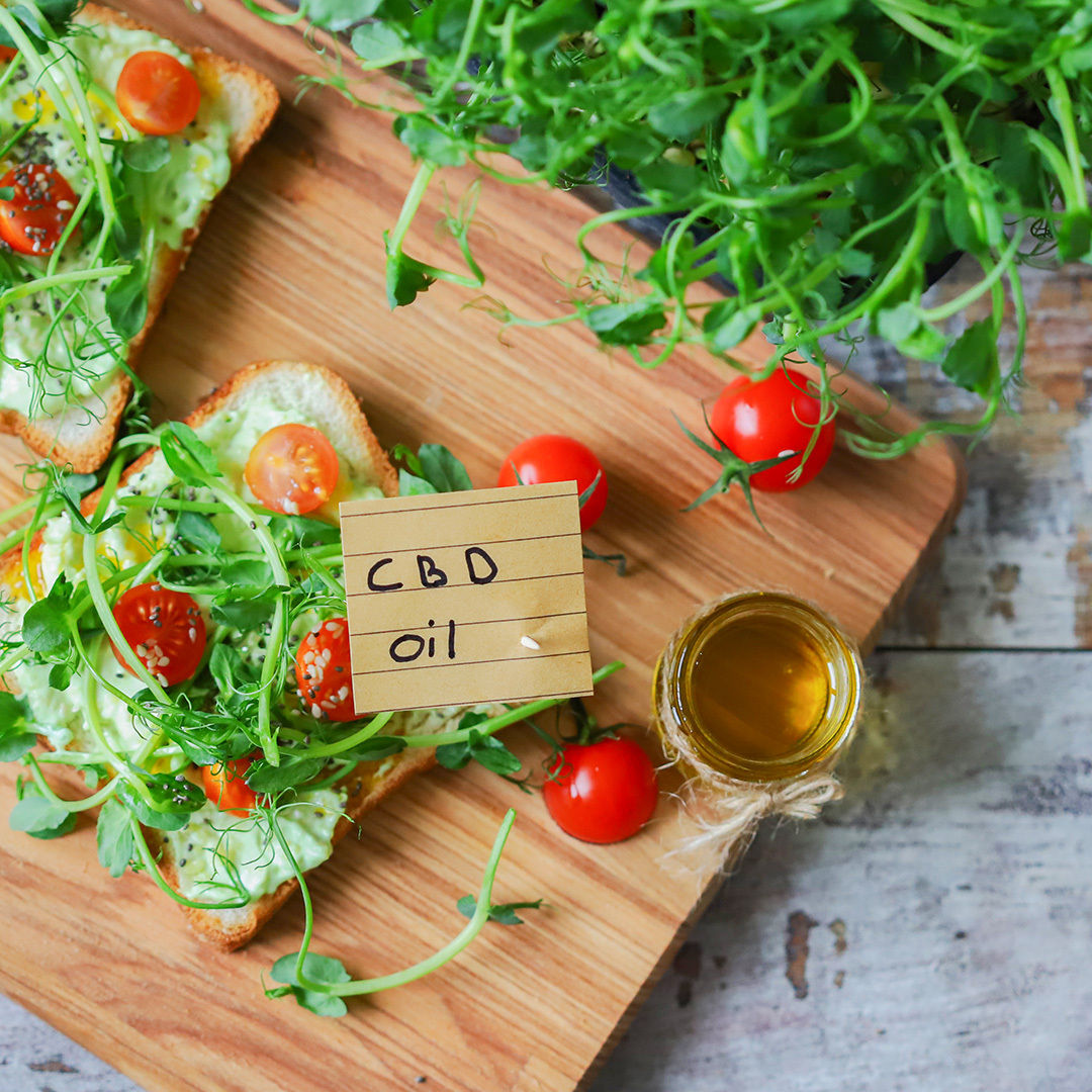 CBD infused sandwich with cherry tomatoes and herbs on wooden board